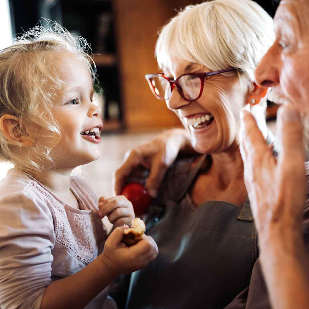 grandparents hold their toddler granddaughter as she laugh and clings to her snacks