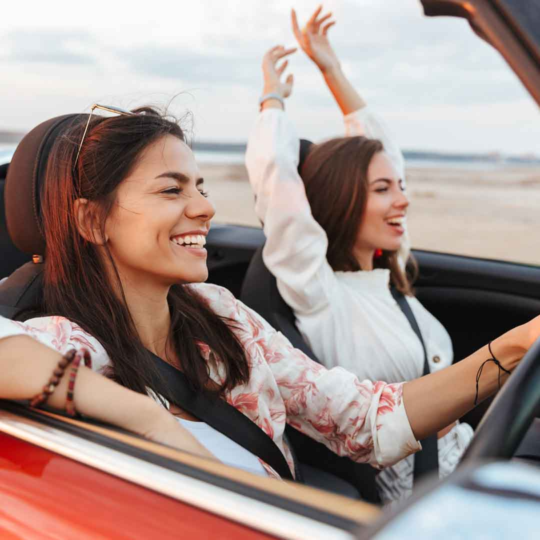 two women enjoy riding in a convertible with the top down near a beach