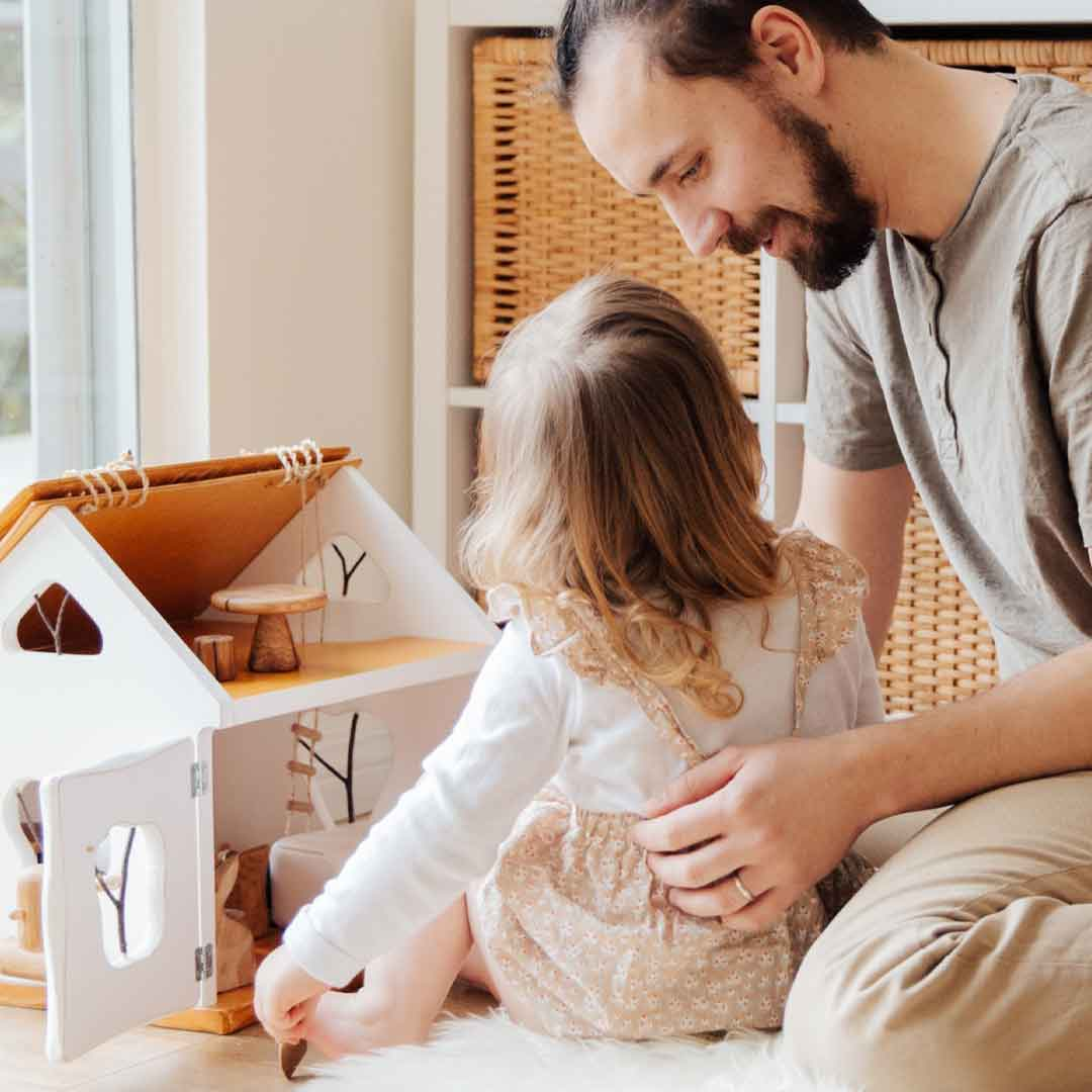 a father holds his toddler daughter as they play with a dollhouse in her bedroom