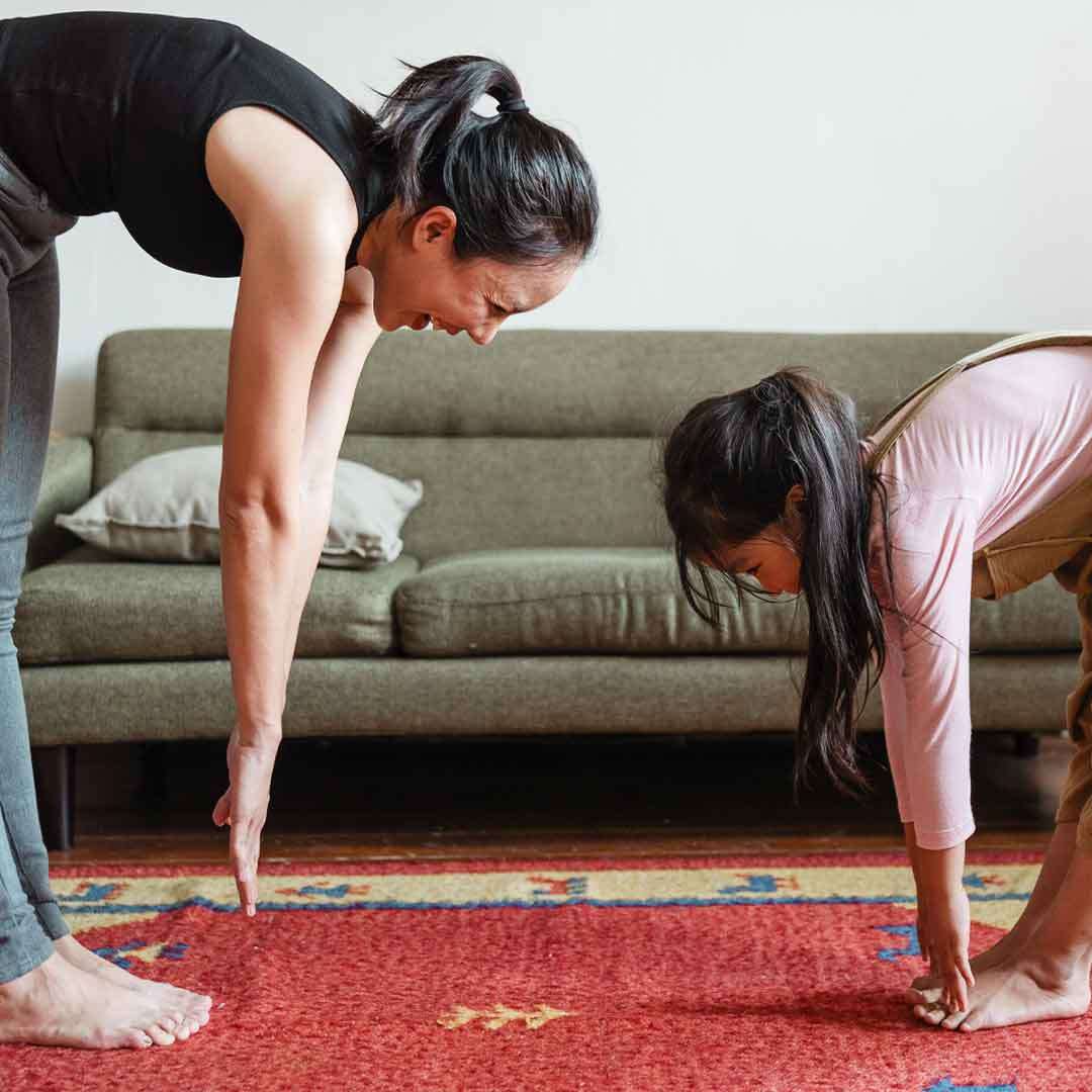 Mother and young daughter stretch by touching their fingers to their toes on red vintage rug in living room