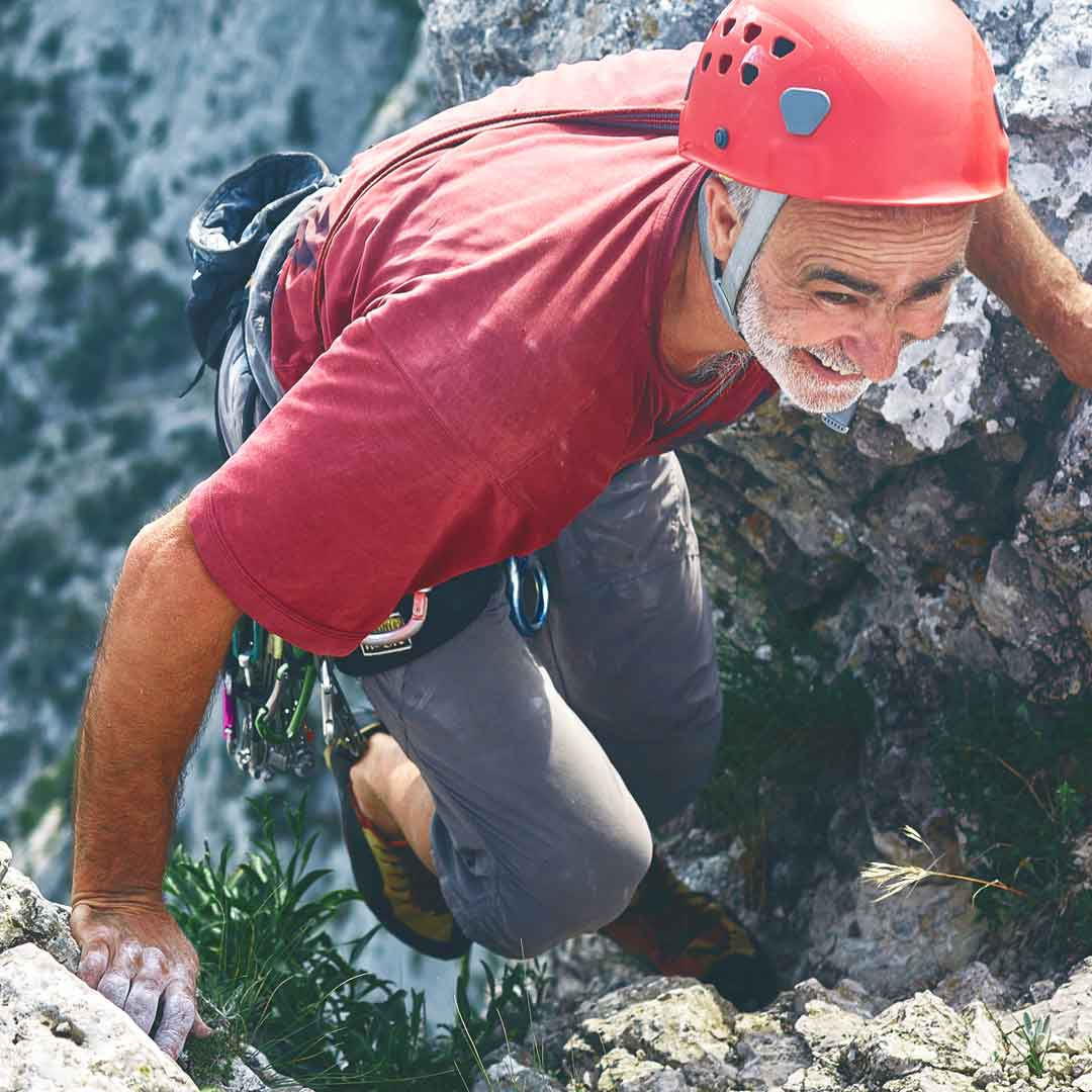 smiling man wears helmet and harness as he nears the top of a mountain