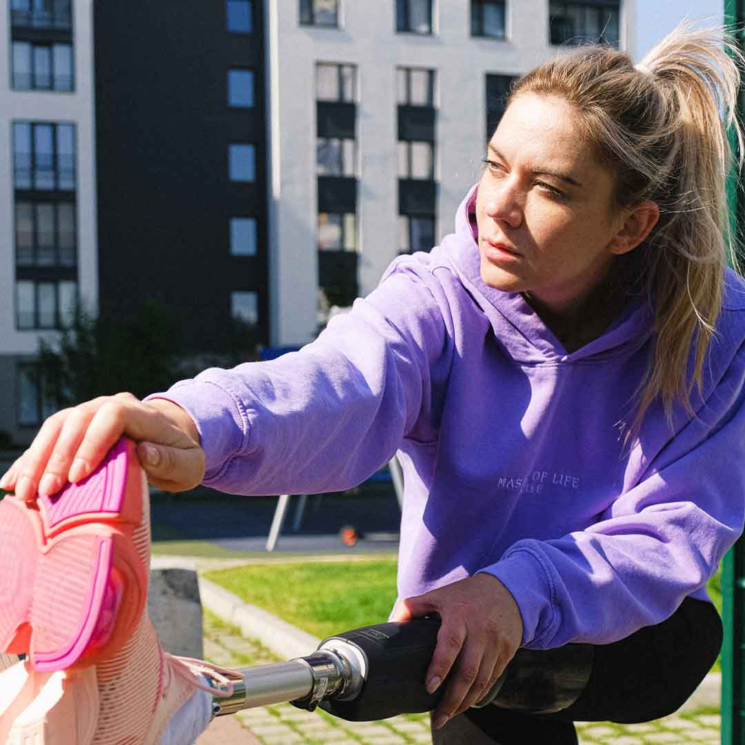 woman with prosthetic leg stretches on lawn outside her apartment building