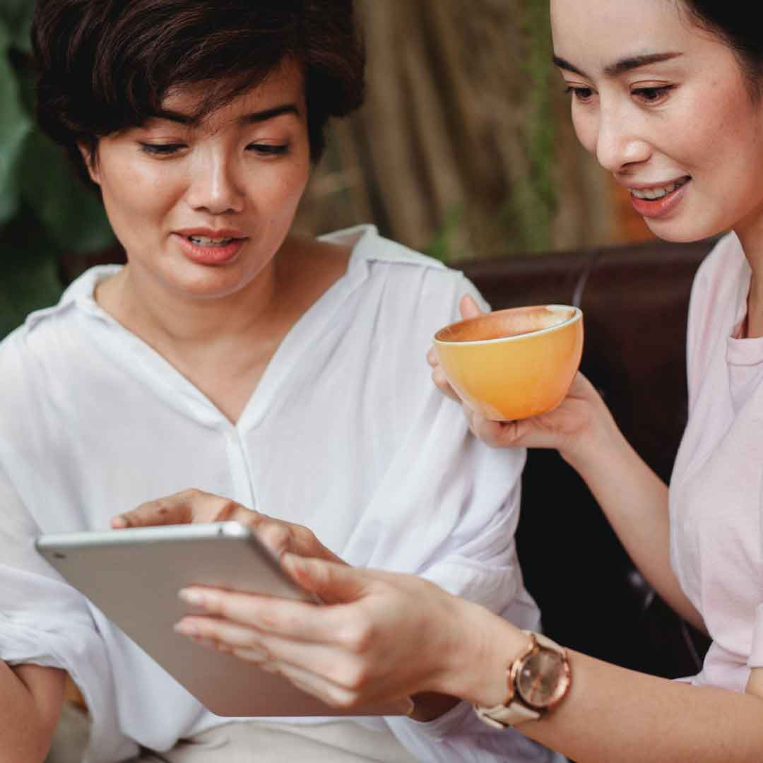 two ladies sip tea and navigate tablet screen together