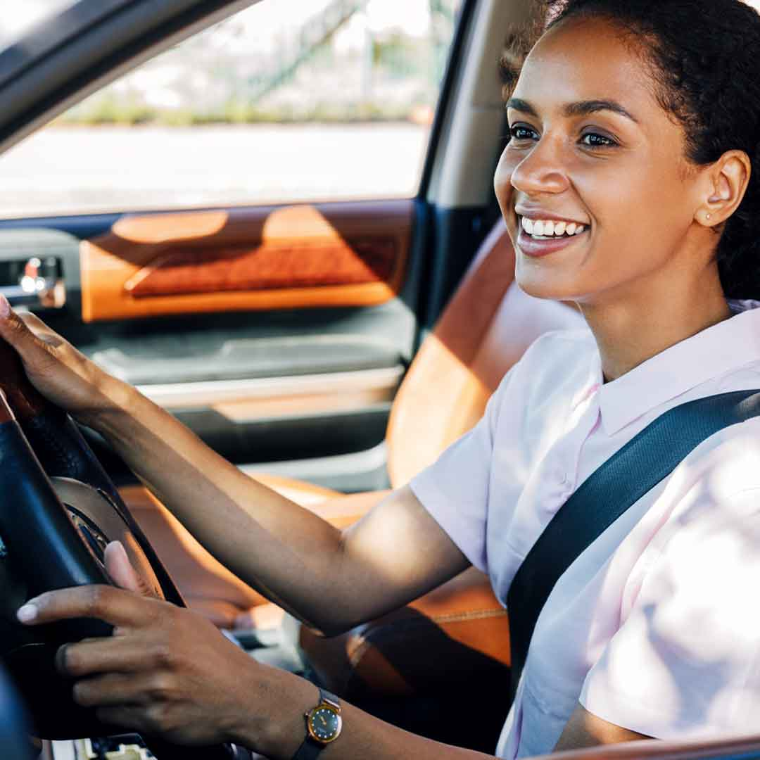 a woman drives her car with leather seats, wears her seatbelt, and looks happily at the road ahead