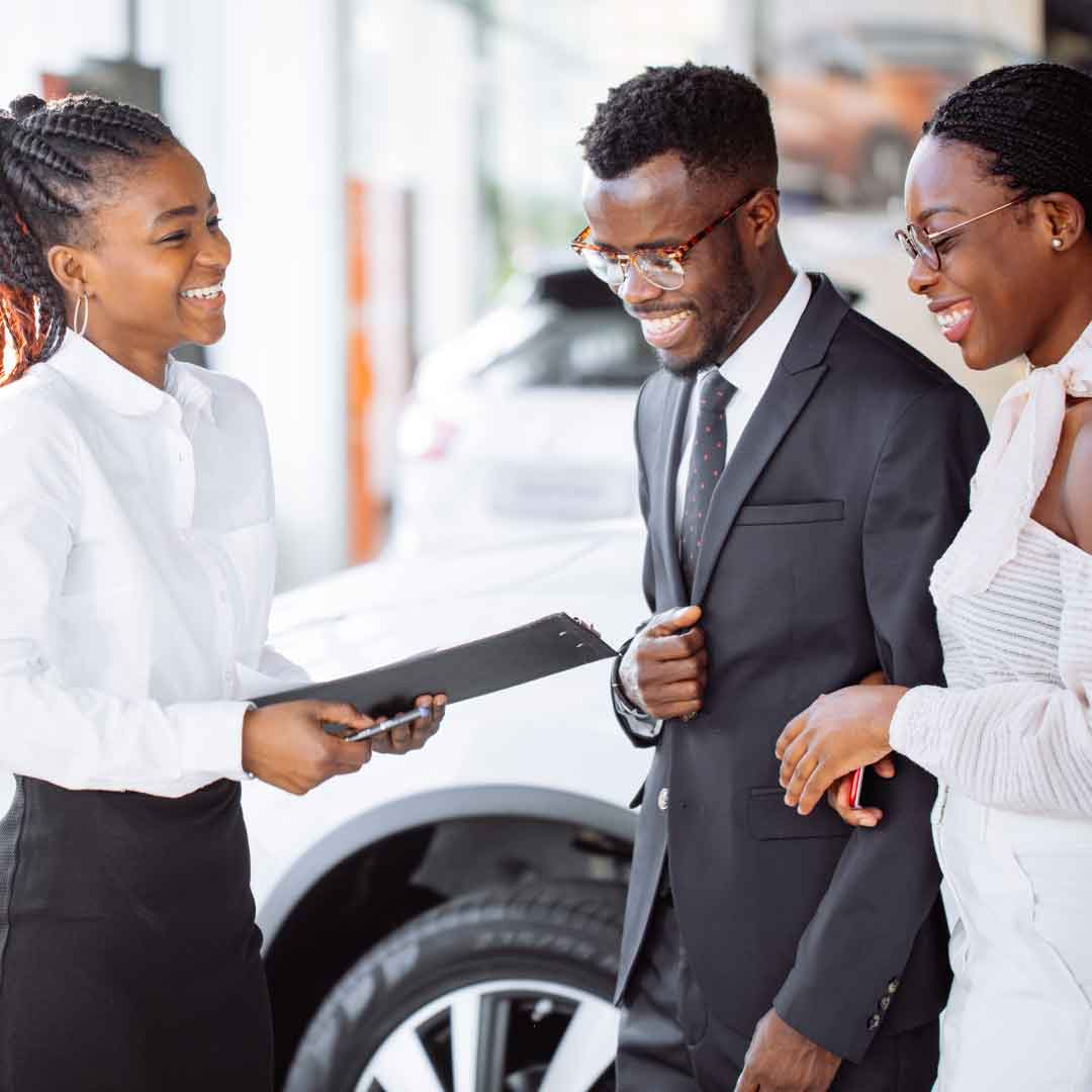 a young, stylish man wearing a suit and a woman wearing a white dress laugh while chatting with the car saleswoman in the well-lit car showroom