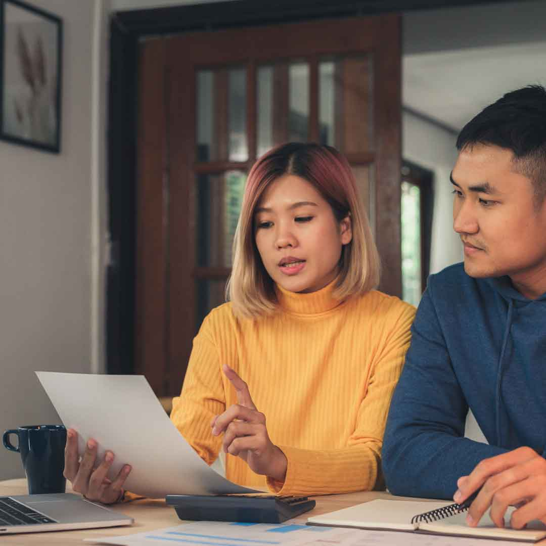 a young couple reviews their budget and paperwork together at the dining table