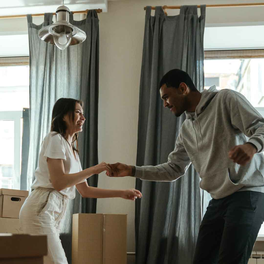 a young man and woman take a dance break while unpacking their belongings in a new home