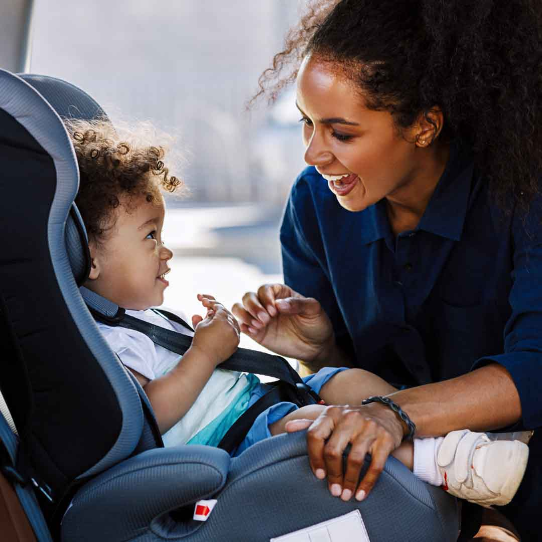woman smiles at baby while securing carseat seat belt