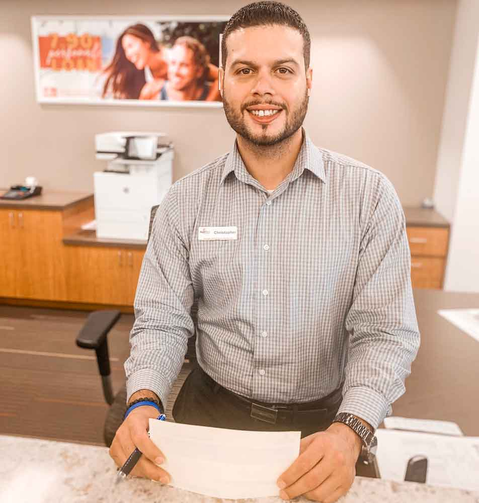 portrait of smiling and welcoming male SunWest branch representative at teller station