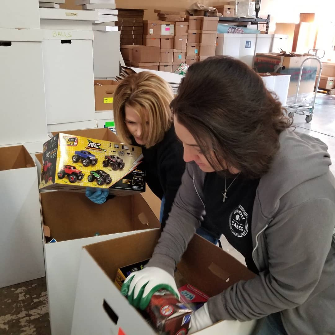 two SunWest employees volunteering with SunWest Cares dig through cardboard boxes to sort donations at a local collection center