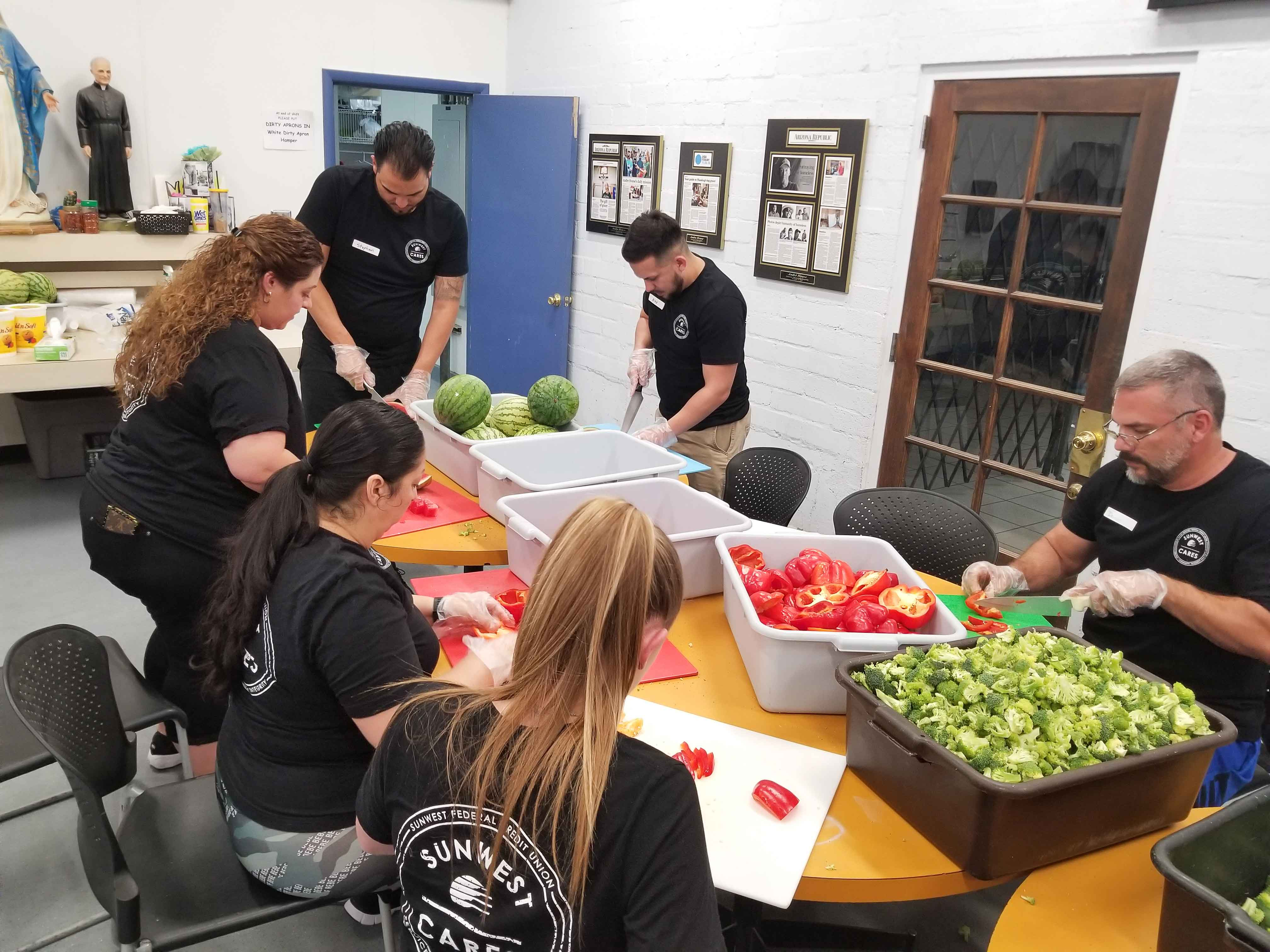 six SunWest employees volunteering with SunWest Cares cut fruit to prepare lunch at Andre House in Phoenix