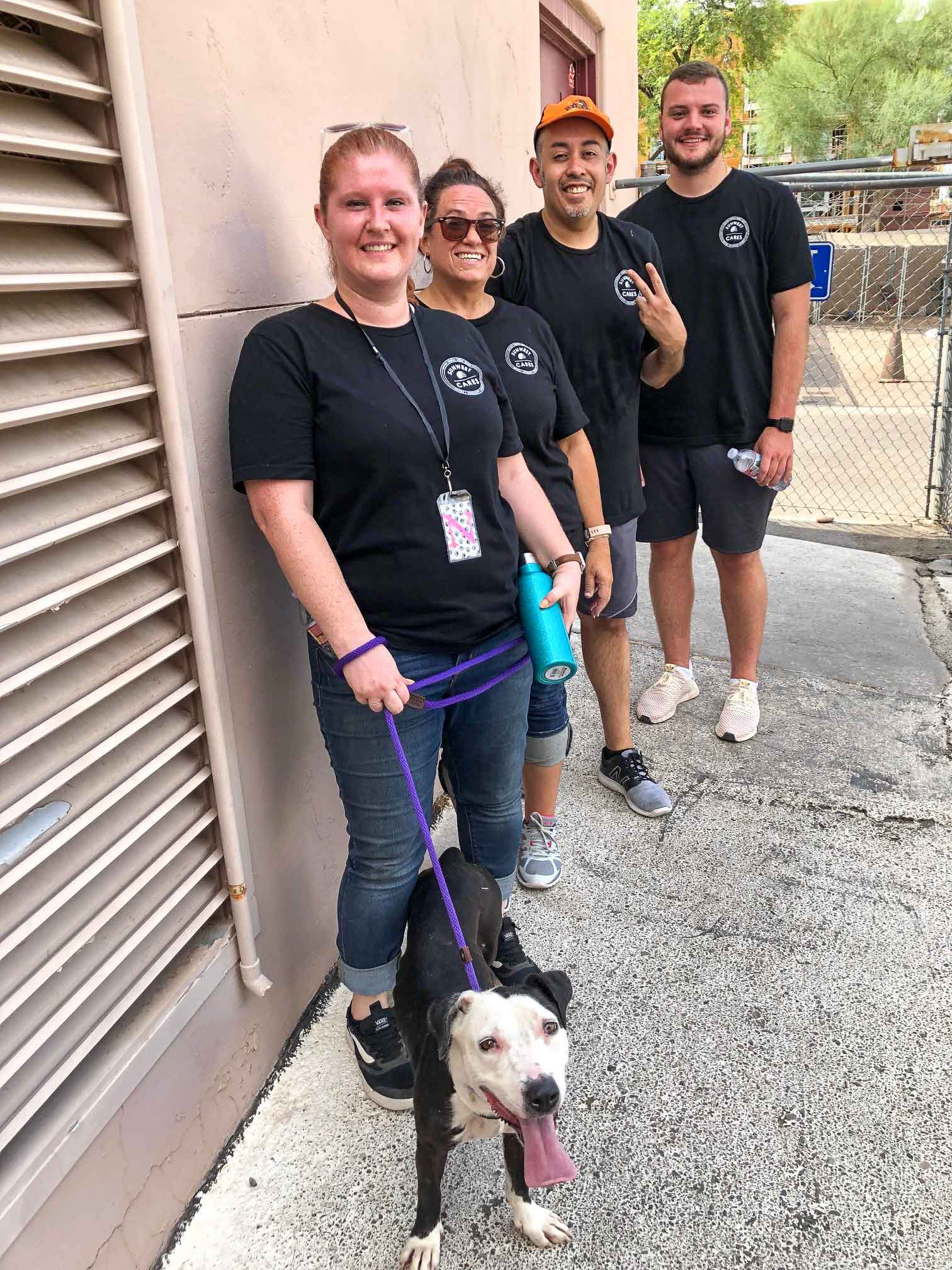 four SunWest employees smile and pose with a brown and white dog on a leash as they volunteer with SunWest Cares at the Maricopa Animal Shelter