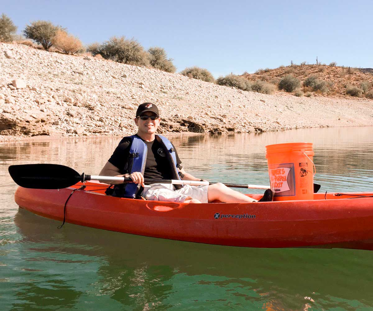smiling SunWest employee kayaks on lake pleasant to collect and dispose of trash while volunteering with SunWest Cares