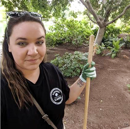 SunWest employee volunteering for sunwest cares smiles while holding rake under a shady tree in the Japanese Friendship Garden in downtown Phoenix