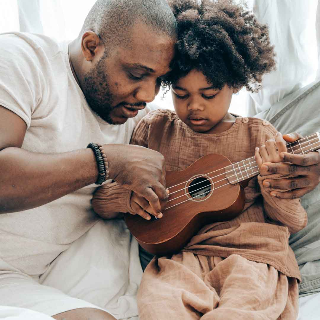 father places son's fingers on ukulele to teach him how to play while relaxing at home