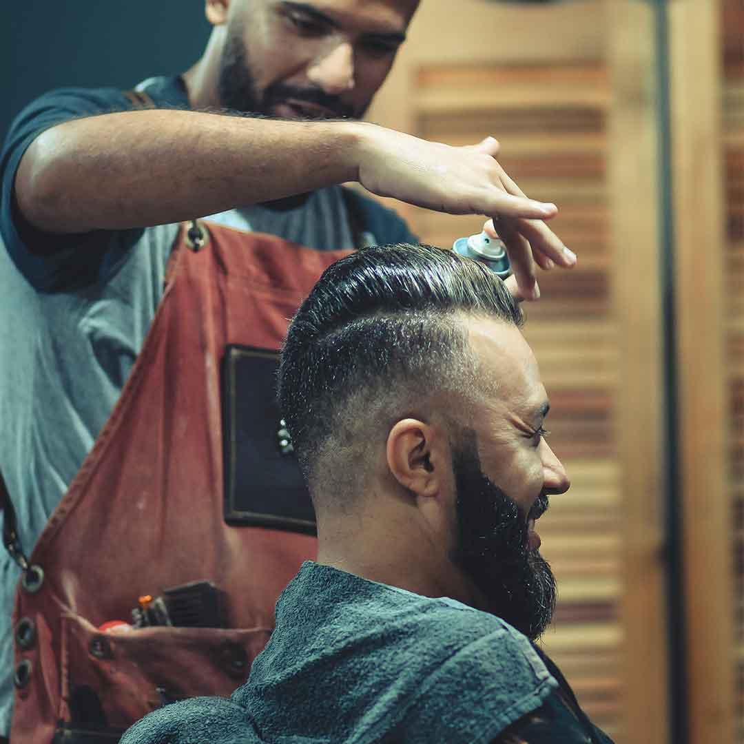 smiling man with beard getting his hair cut by a barber in an industrial-style barbershop