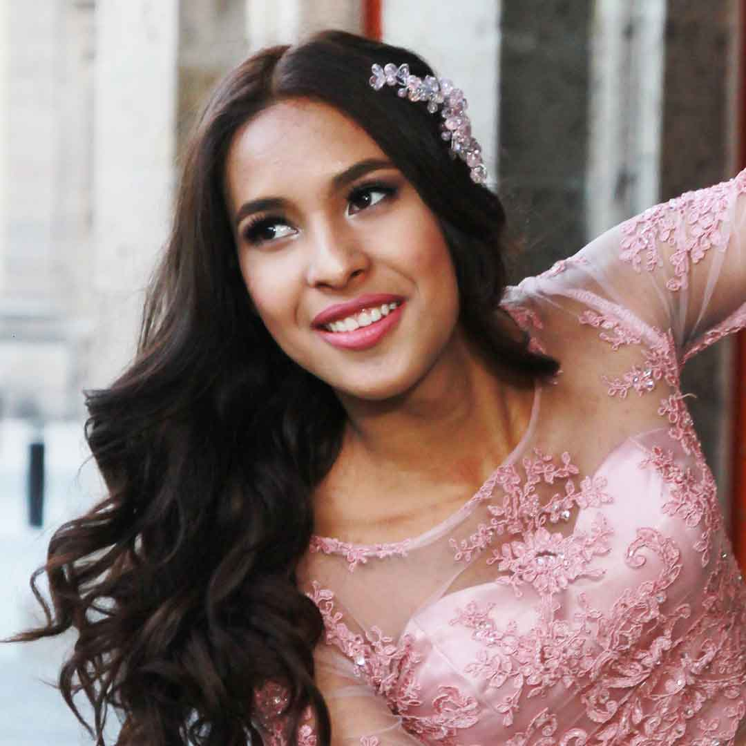 teenage woman with formal pink dress andd flowers in her hair ready for her Quinceañera