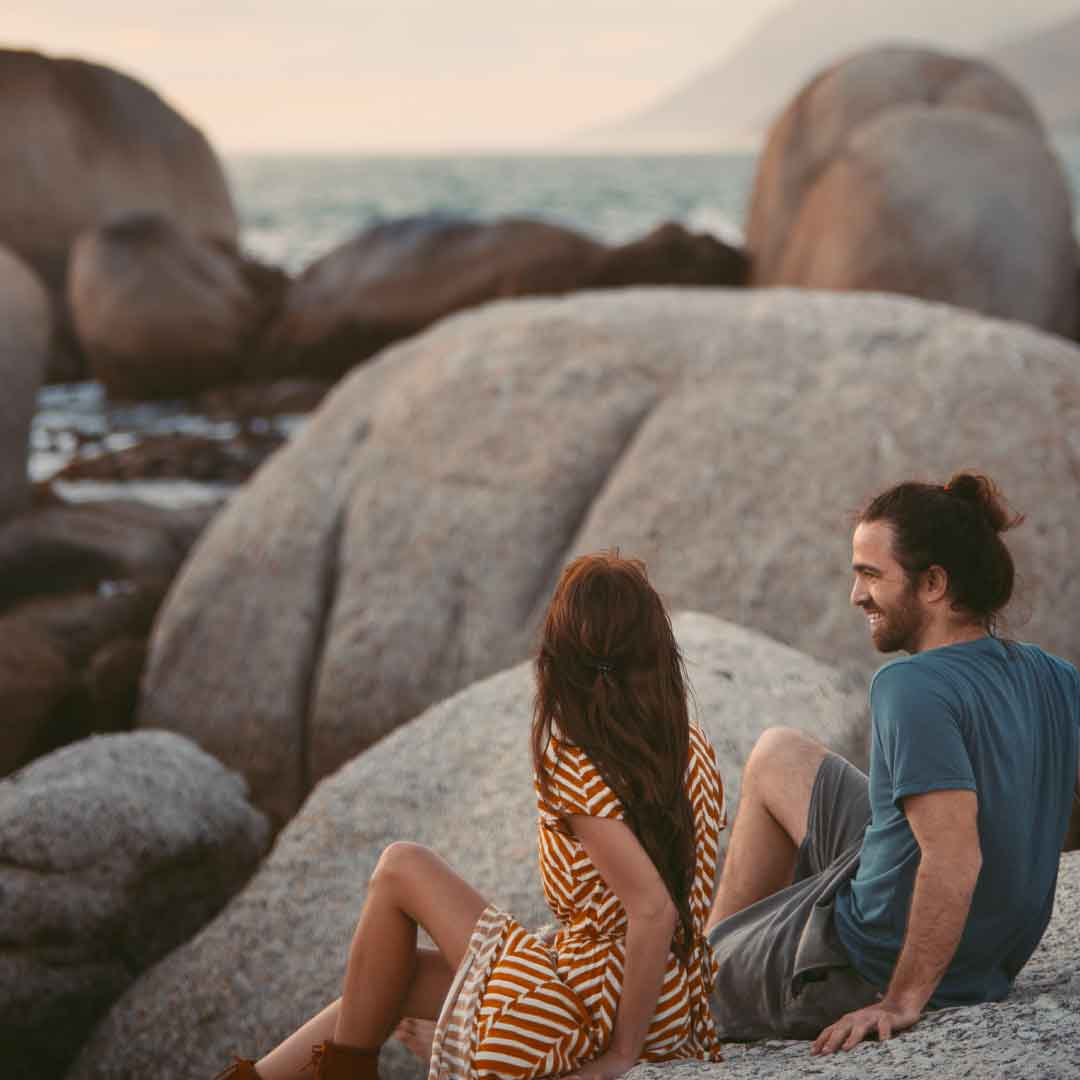 young man and woman chatting while sitting on boulders by the beach and watching the sunset
