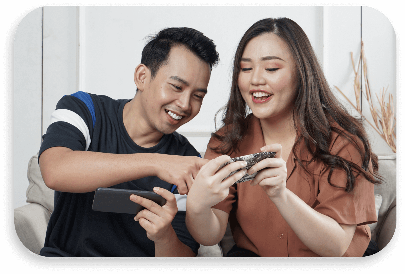 Photo of a couple having fun... playing mobile game!