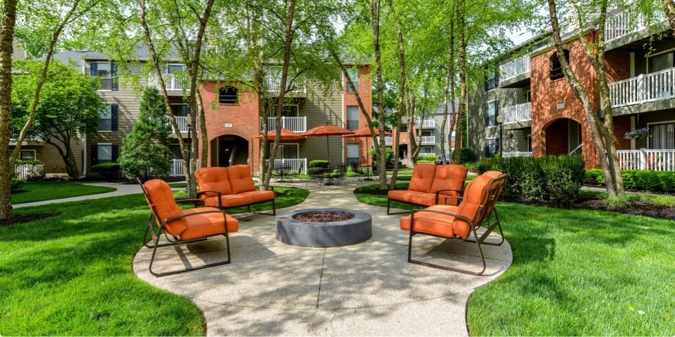 Outdoor fire pit surrounded by lounge chairs in Maxus Properties courtyard