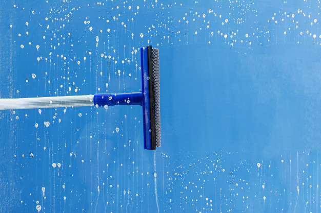 a squeegee cleaning glass