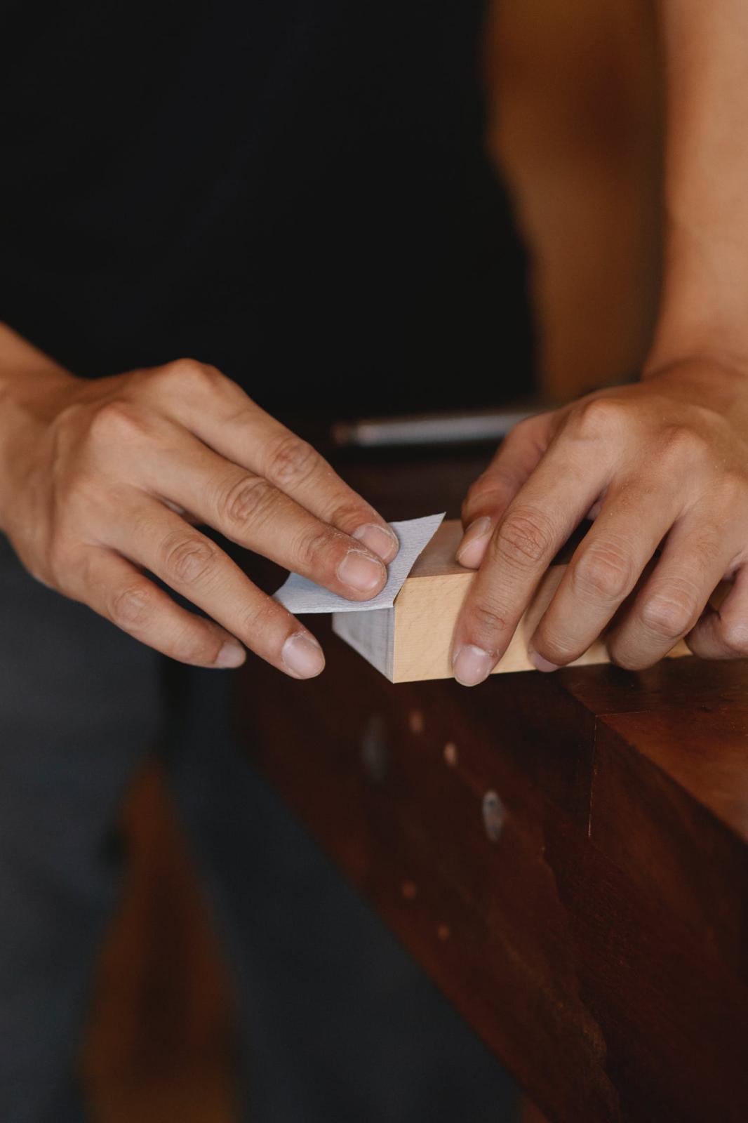man using sandpaper on wood