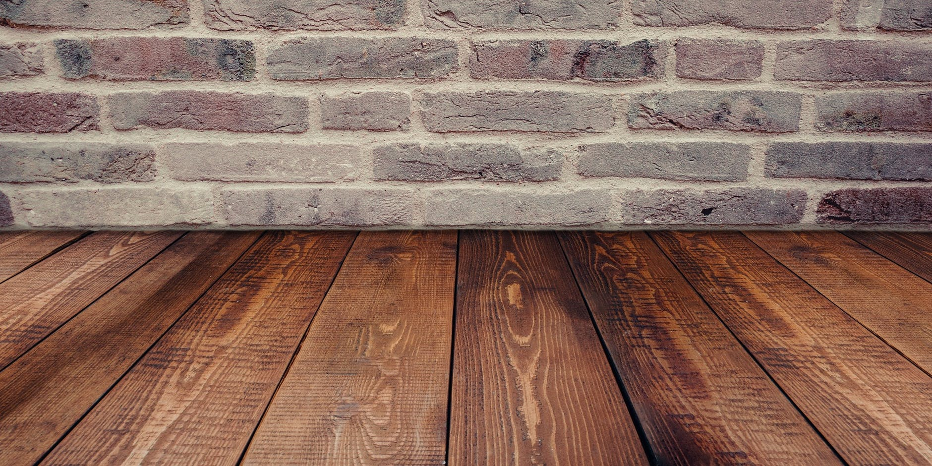 reclaimed wooden planks on floor with brick wall