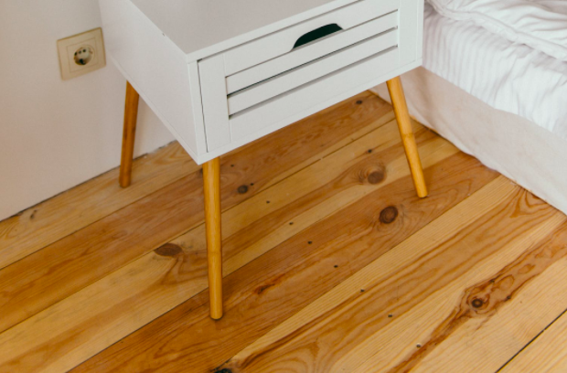 wooden floor in bedroom next to bed and night stand