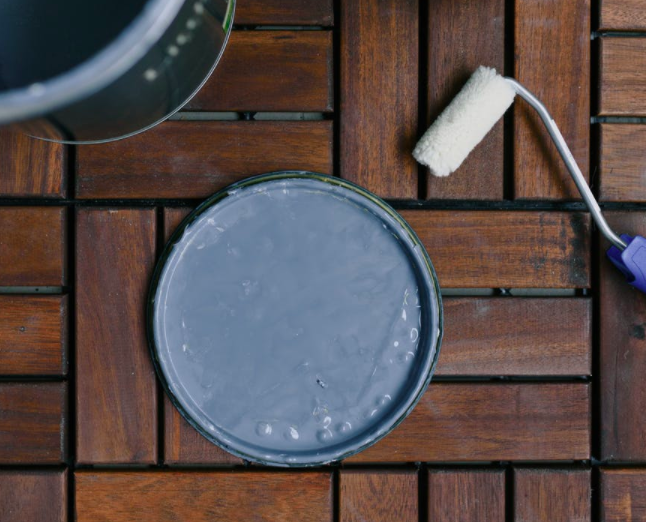Paint bucket and paint roller on wooden floor