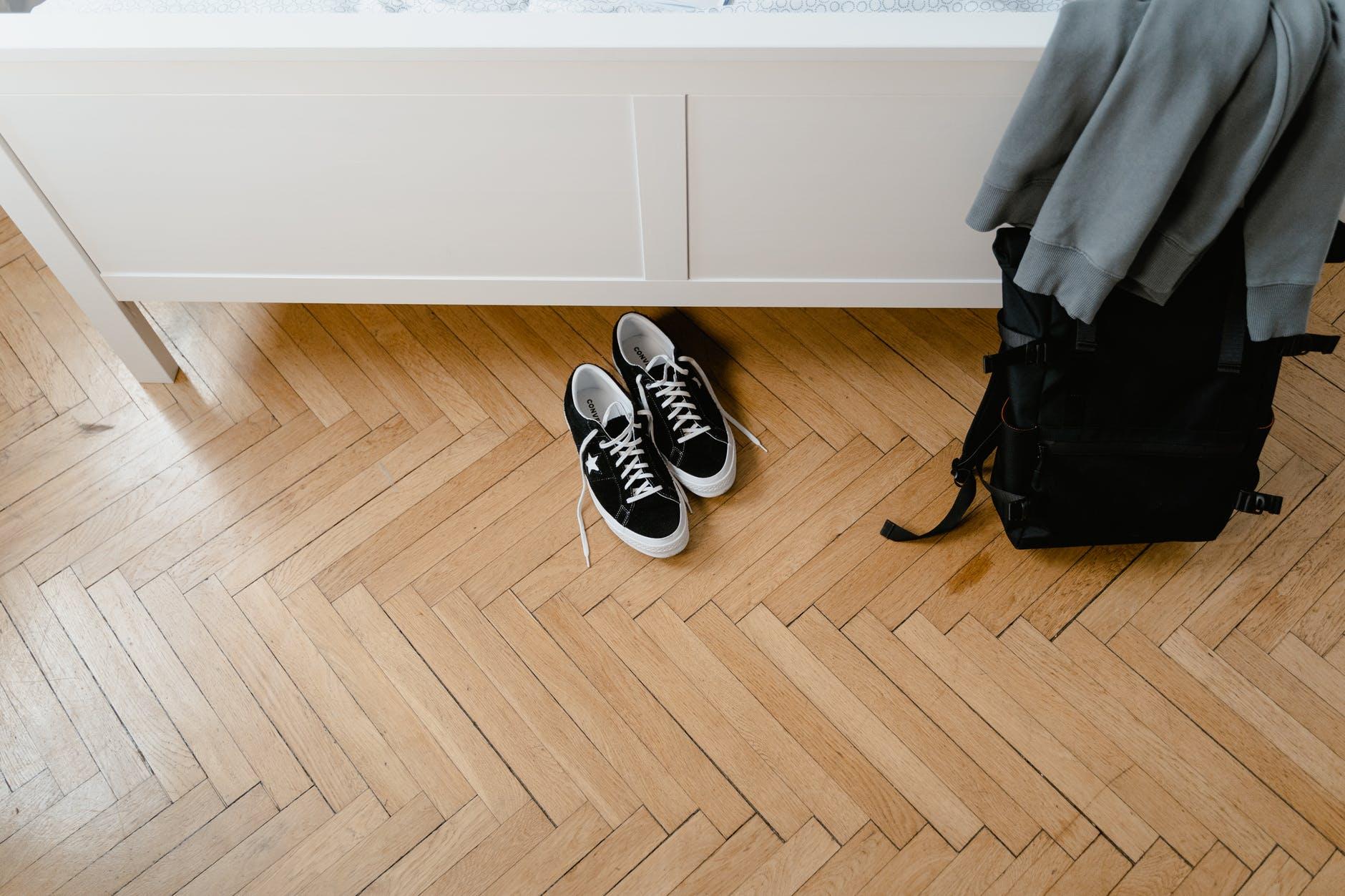 Shoes and backpack on light parquet flooring