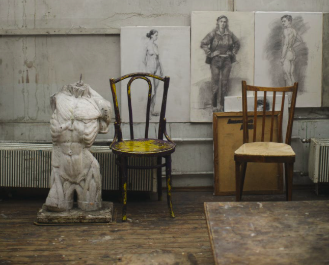 Anatomy statue and sketches in dirty art room.