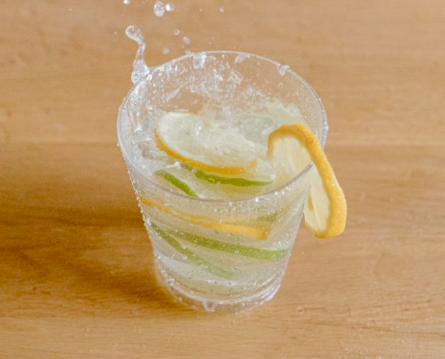 Glass of water with lemon and lime slices splashing.
