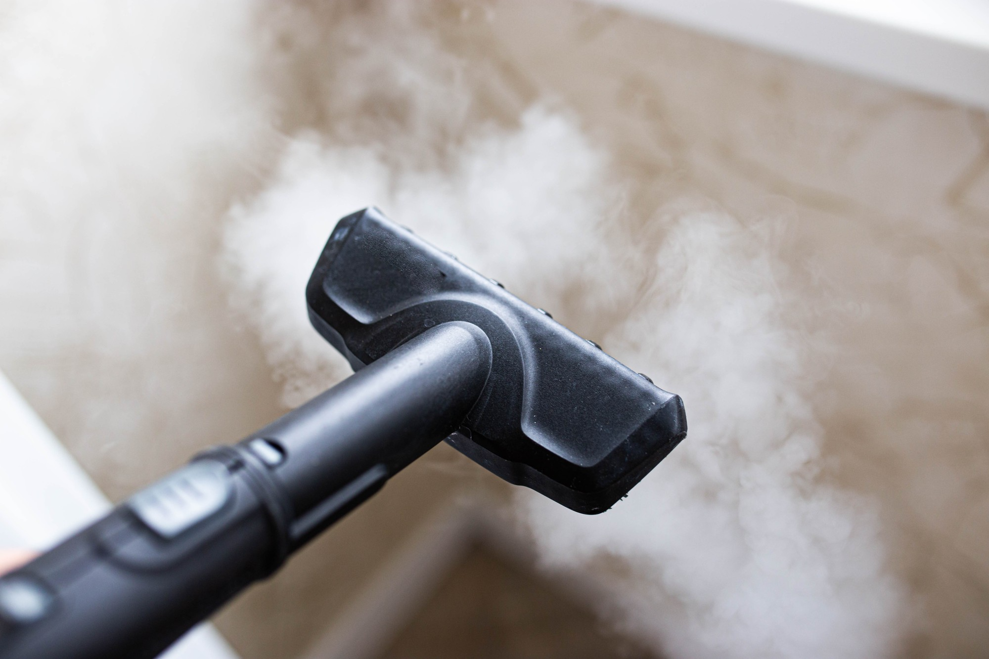 Steam cleaner steaming upholstery