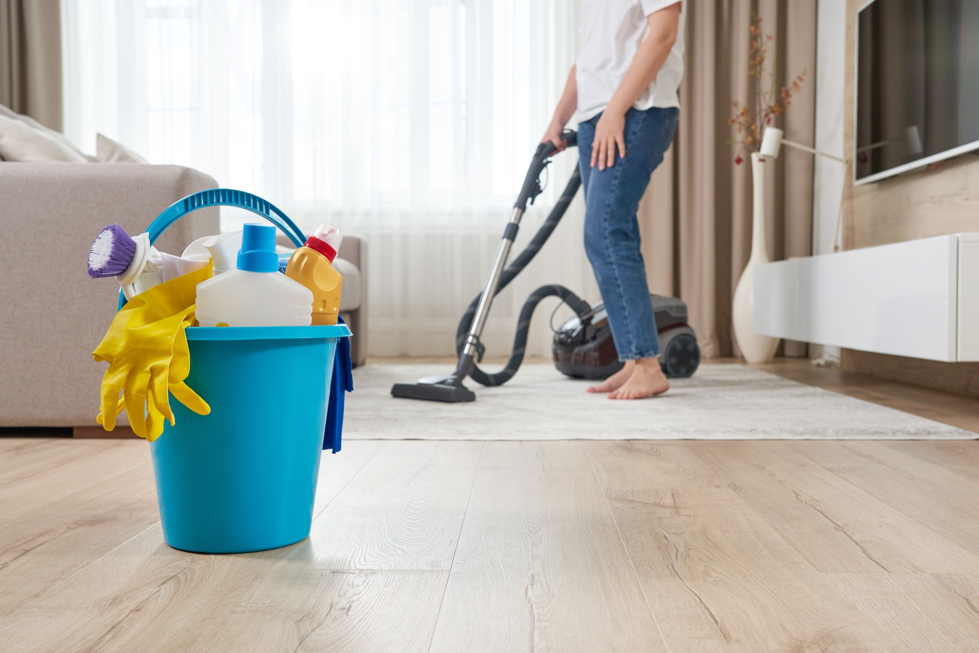 Woman vacuuming rug with bucket of cleaning supplies