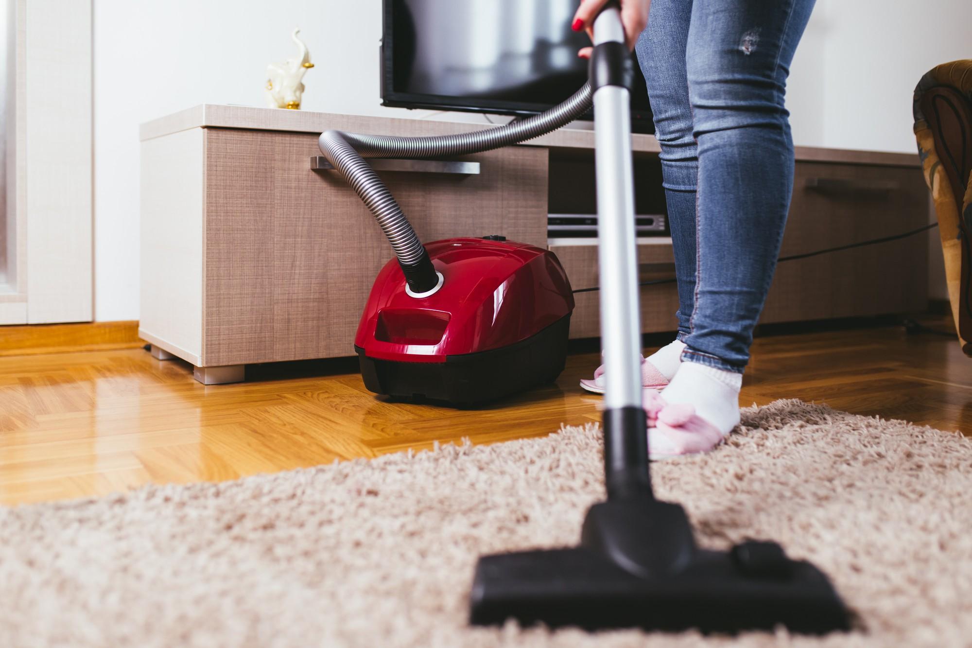 Woman using vacuum cleaner on rug