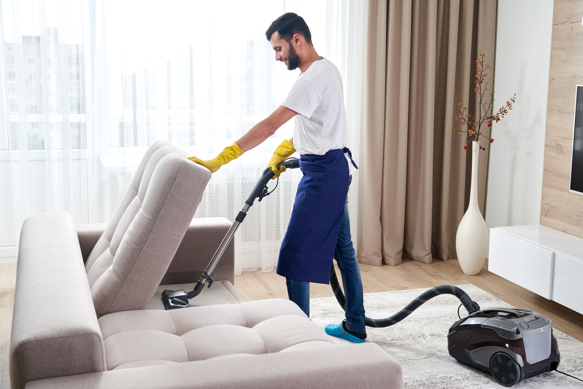 Man cleaning rug under sofa