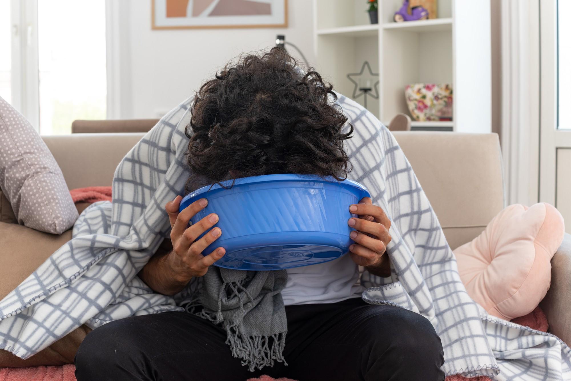 sick person vomiting into a bucket