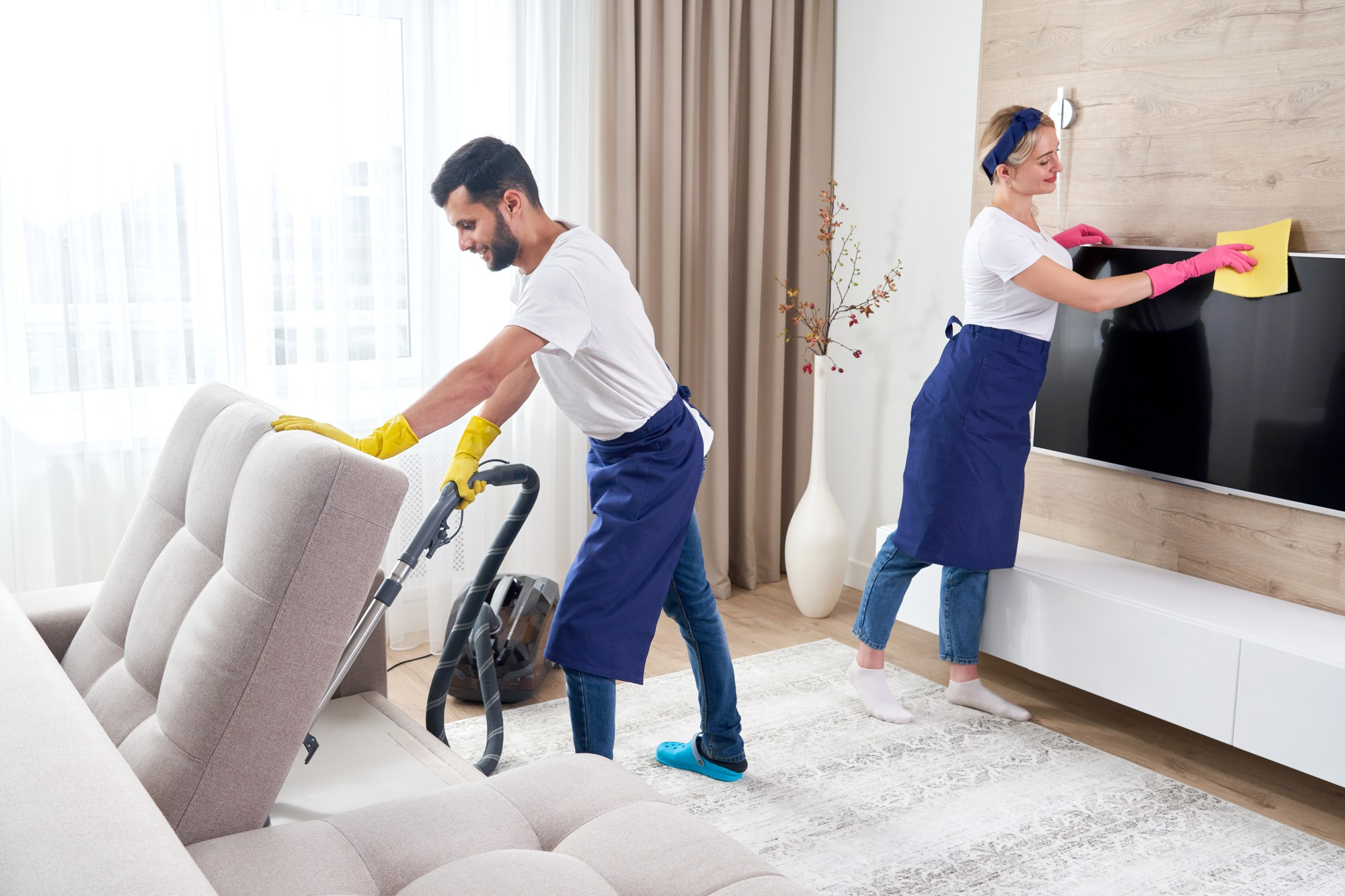 Professional cleaners cleaning the living room area