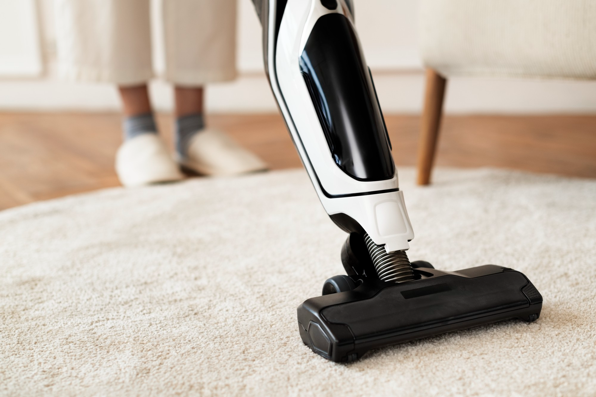 Person vacuuming white rug