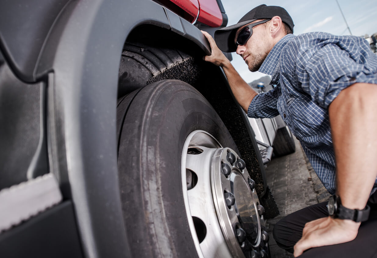A commercial driver inspects the tires of his semi-trailer.