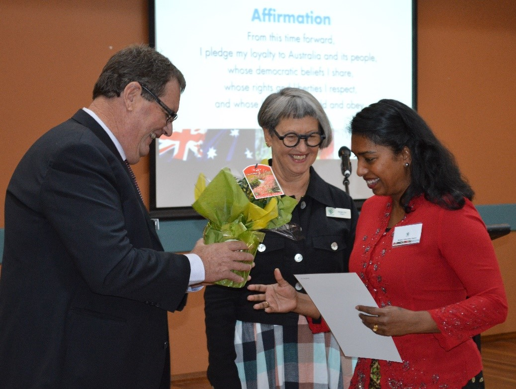 A woman being handed a certificate and plant as two people look on.