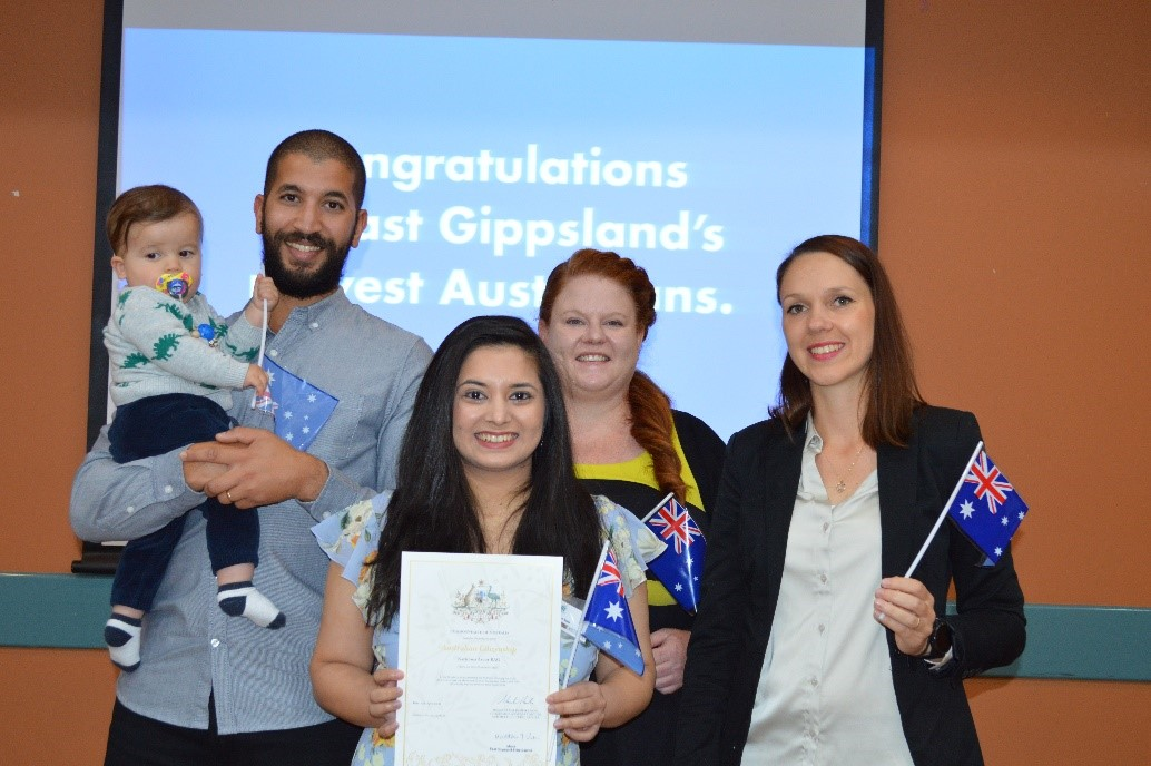 Woman holding certificate standing with four others, holding Australian flags.