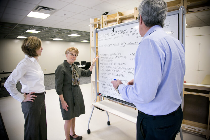 Image of three people discussing  content on a whiteboard presentation
