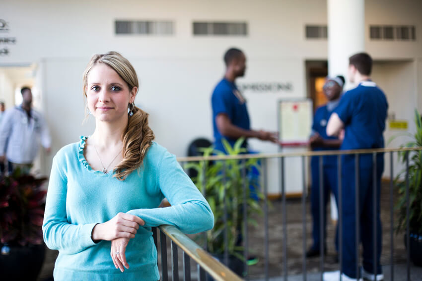 A smiling graduate with a scene of a hospital lobby in the background