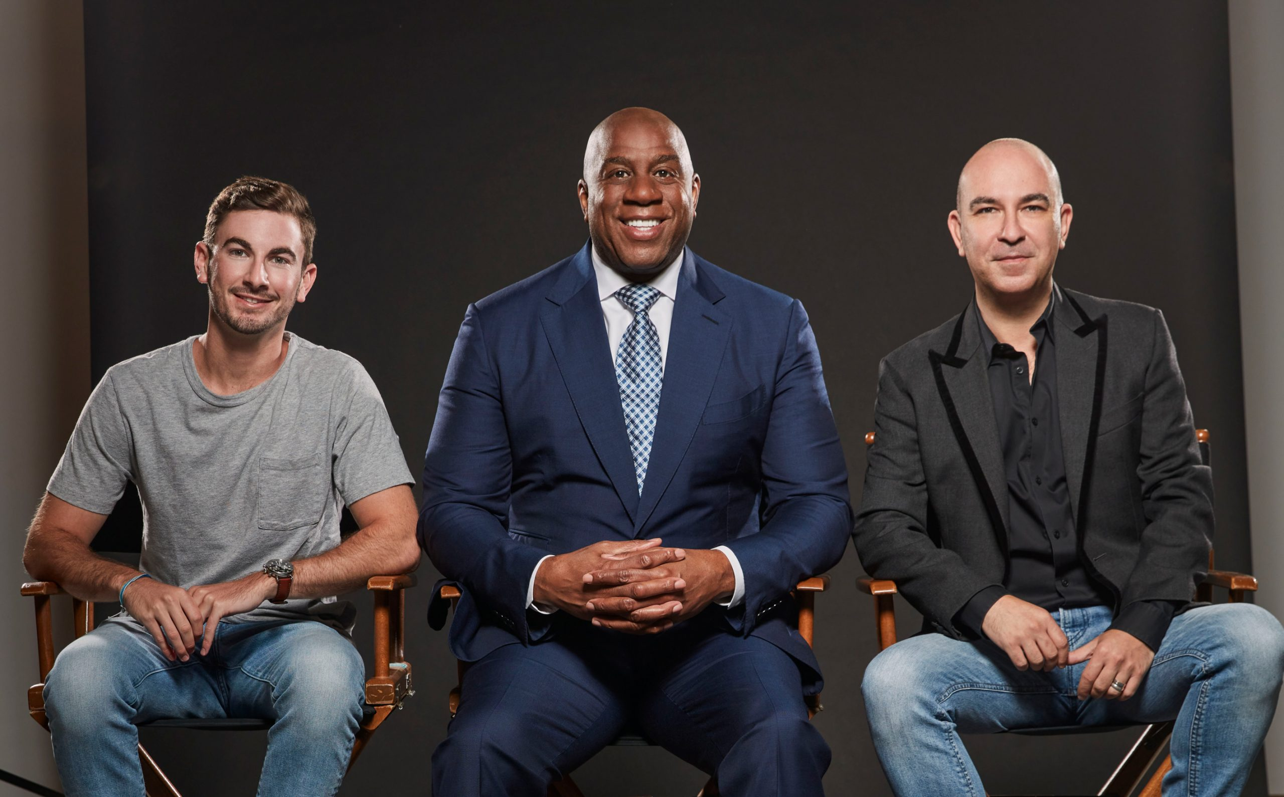 Uncle Bud's founders with Magic Johnson smiling at the camera