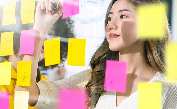 Young woman writing on a glass wall full of sticky notes