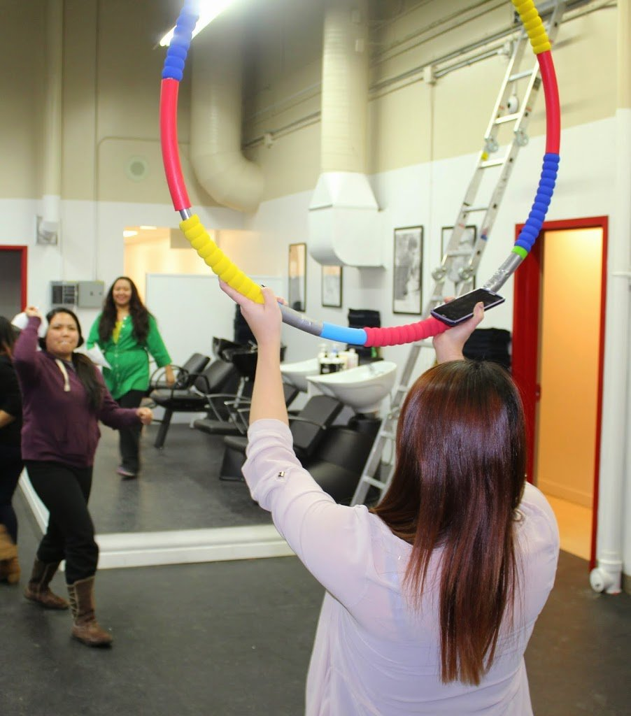 People throwing paper airplanes through a colorful hoop.