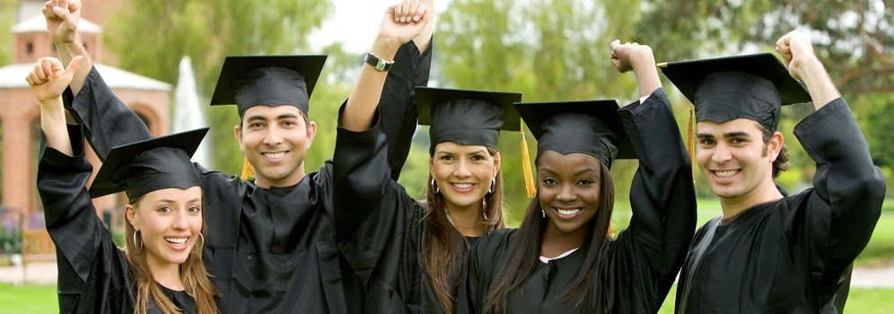 Students graduating in a field with their hats on.