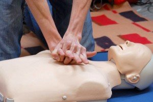 A person performing CPR on a mannequin.