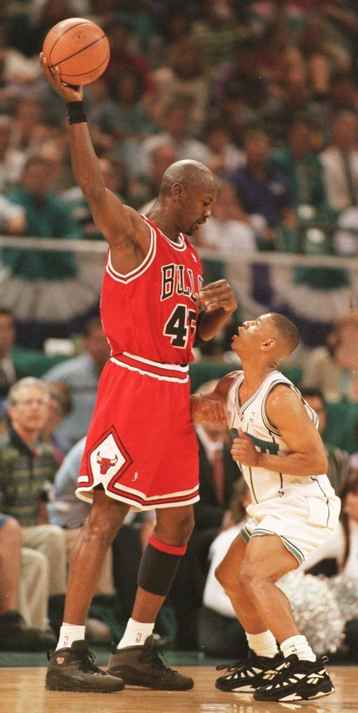 Michael Jordan towering over the shortest player in the NBA Muggsy Bogues